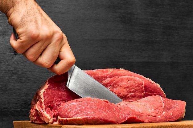 Mão de homem closeup cortando uma carne de bovino com uma faca em um fundo preto