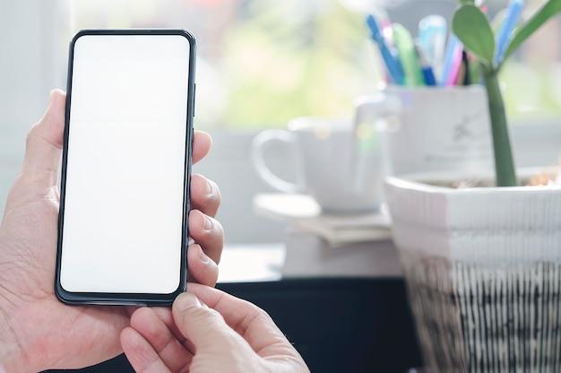 Mão de homem closeup segurando o smartphone com tela branca em branco enquanto trabalhava na mesa de escritório