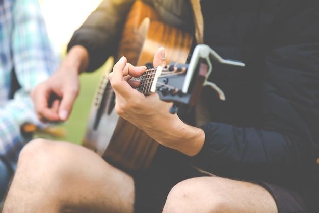 Mão de homem closeup tocar guitarra. mulher caucasiana e homem bonito estão passando algum tempo juntos no acampamento da natureza e tocam guitarra.