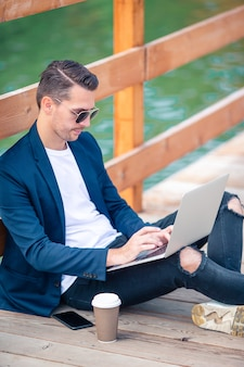 Mão de homem closeup trabalhando na ponte de madeira com laptop