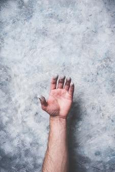 Mão de homem coberta com tinta no fundo da parede de concreto cinza
