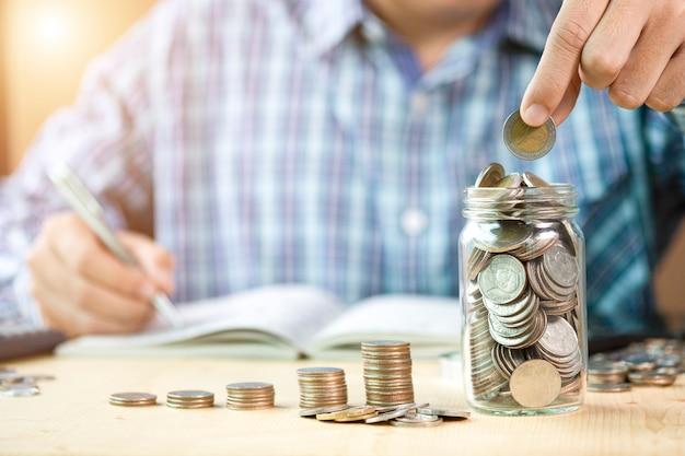 Mão de homem colocando moedas para jarra com empilhamento de moedas