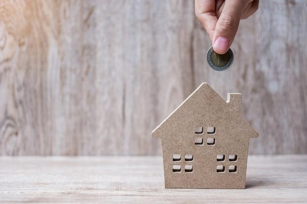 Mão de homem colocando moedas sobre o modelo de casa em fundo de madeira.