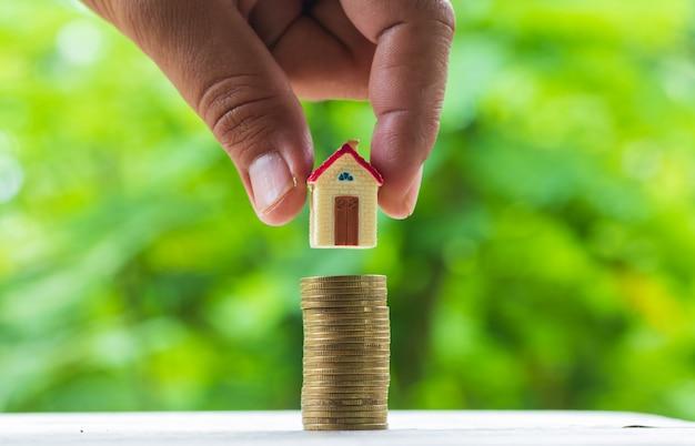 Mão de homem colocando o modelo da casa na pilha de moedas. conceito de escada de propriedade, hipoteca e investimento imobiliário.