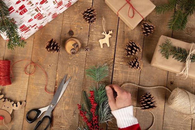 Mão de homem, colocando uma mordida de natal na mesa de trabalho de madeira vintage.
