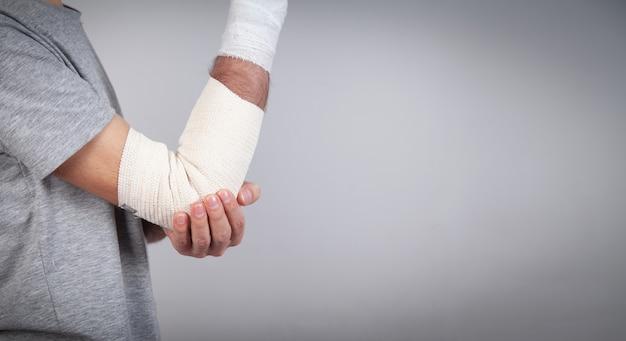 Mão de homem com bandagem elástica no cotovelo.