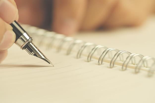 Mão de homem com caneta escrevendo no notebook