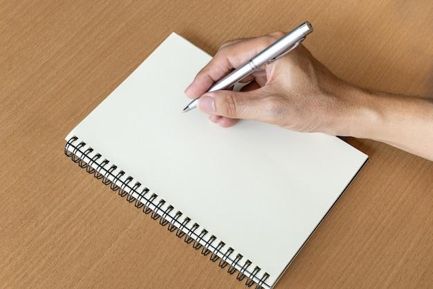 Mão de homem com caneta prepare-se para escrever no caderno