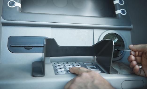 Mão de homem com cartão de crédito. atm. retirar dinheiro