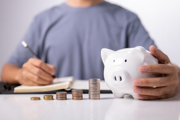 Mão de homem com cofrinho na mesa branca, economizando dinheiro, riqueza e conceito financeiro