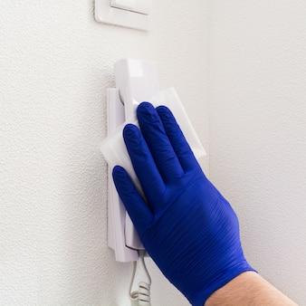 Mão de homem com luva azul lavando interfone com guardanapo úmido