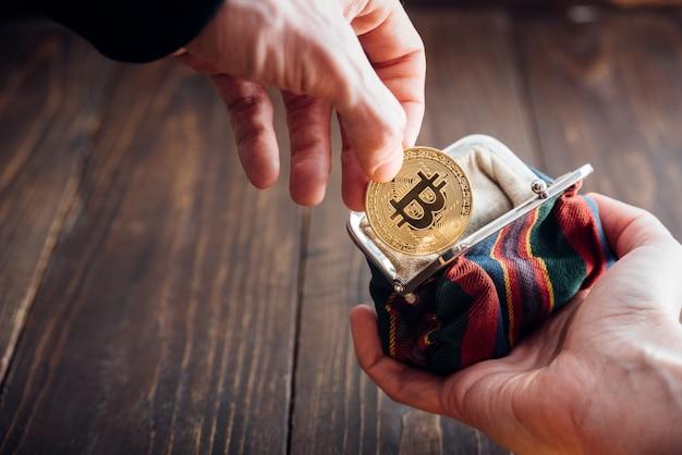 Mão de homem com moeda. símbolo bitcoin