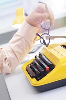 Mão de homem com óculos digitando em uma máquina de escrever amarela na mesa de escritório branca