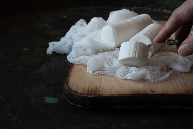 Mão de homem cortando, fatiando, com faca queijo de cabra francês, queijo de pasta mole, aperitivo tradicional, lanche, sobremesa sobre fundo rústico de metal