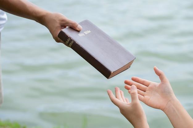 Mão de homem dando a bíblia às mulheres. conceito de dar