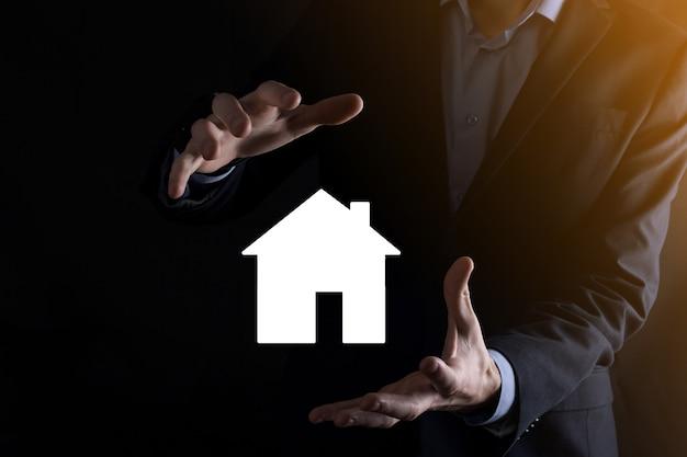 Mão de homem de empresário segurando o ícone da casa na parede azul. conceito de seguro e segurança de propriedade. conceito de bens imobiliários. bandeira com espaço de cópia.