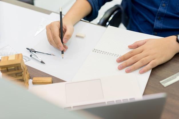 Mão de homem de engenharia usando lápis para escrever