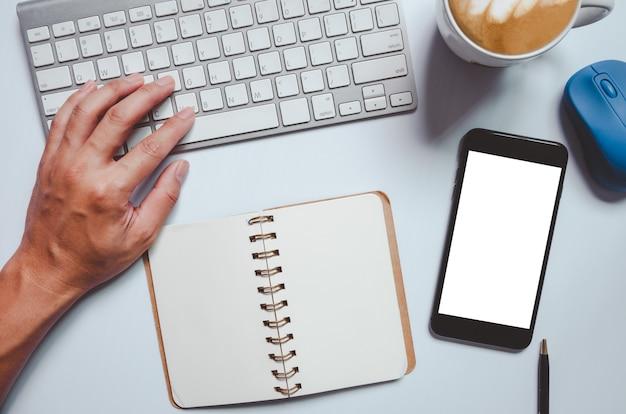 Mão de homem de maquete de telefone celular usando livro de notas, caneca de café e mouse do teclado do computador