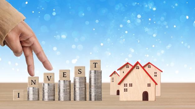 Mão de homem de negócios andando no empilhamento de moedas na mesa de madeira com a casa modelo e bloco de cubo de madeira com a palavra investir.