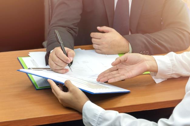 Mão de homem de negócios assinando no documento com o parceiro