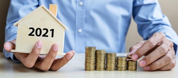 Mão de homem de negócios colocando moeda de ouro na escada de dinheiro crescente com casa de madeira