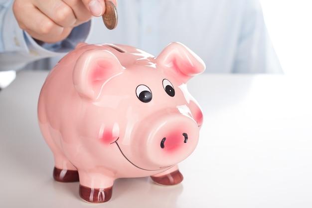 Mão de homem de negócios colocando moeda no cofrinho rosa engraçado