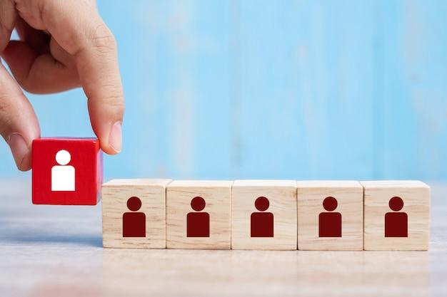 Mão de homem de negócios colocando ou puxando o bloco de madeira vermelho com o ícone de pessoa branca no edifício.