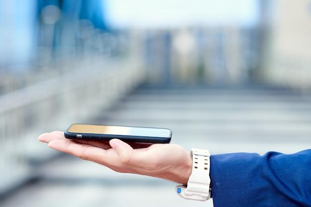Mão de homem de negócios com telefone. renderizar apresentação de inicialização.