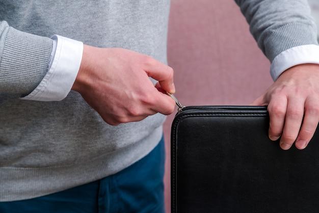 Mão de homem de negócios jovem puxando um zíper para fechar um laptop de couro preto.