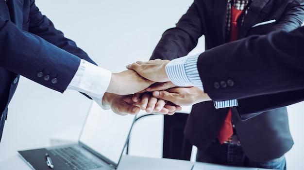Mão de homem de negócios juntou-se à equipe no escritório com colegas.