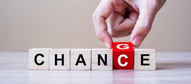 Mão de homem de negócios lançando blocos de cubo de madeira com texto de mudar para chance