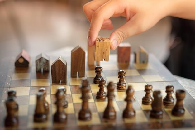 Mão de homem de negócios, movendo-se de xadrez para o edifício e casa modelos no jogo de xadrez