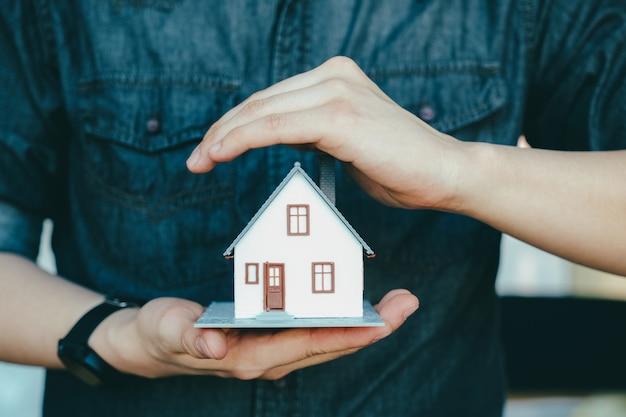 Mão de homem de negócios segura o modelo de casa, salvando a casa pequena.