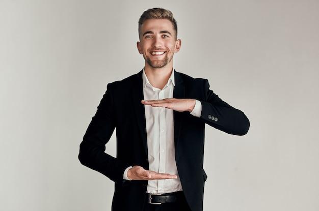 Mão de homem de negócios segurando fundo cinza e sorrindo