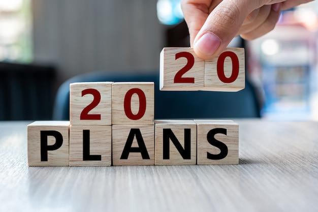 Mão de homem de negócios segurando o cubo de madeira com planos 2020