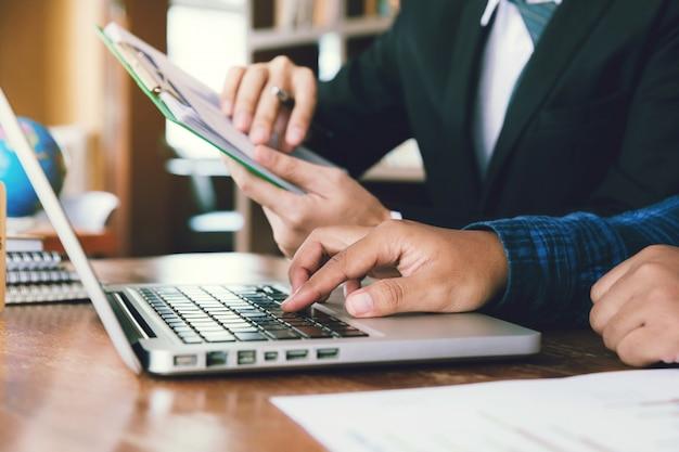 Mão de homem de negócios segurando o gráfico gráfico e apontando gráfico gráfico para analisar o plano de vendas da empresa no escritório. e parceiro, examinando os dados de mercado em laptops.