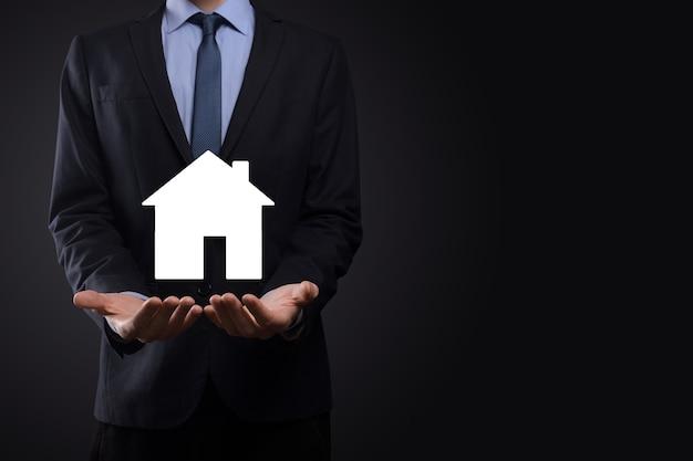 Mão de homem de negócios segurando o ícone da casa sobre fundo azul. conceito de seguro e segurança de propriedade. conceito de bens imobiliários. bandeira com espaço de cópia.