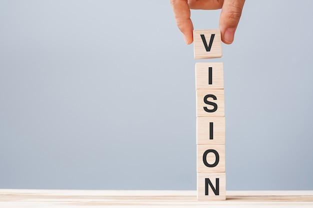 Mão de homem de negócios segurando um bloco de cubos de madeira com a palavra visão de negócios no fundo da mesa. conceito de estratégia, missão e valores essenciais