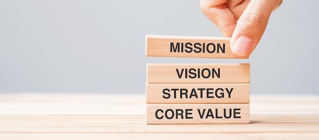 Mão de homem de negócios segurando um bloco de madeira com o texto missão, visão, estratégia e valor central