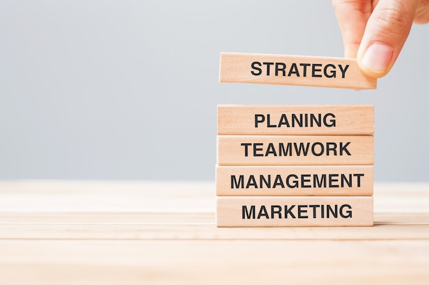 Mão de homem de negócios segurando um bloco de madeira com texto de estratégia, planejamento, trabalho em equipe, gerenciamento e marketing