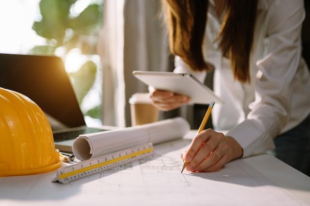 Mão de homem de negócios trabalhando e laptop com projeto arquitetônico no canteiro de obras na mesa do escritório no escritório