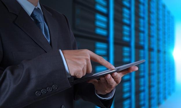 Mão de homem de negócios usando computador tablet e sala do servidor