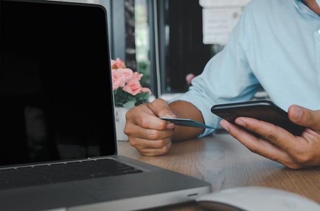 Mão de homem de negócios usando telefone móvel inteligente e cartão de crédito com o laptop na mesa. compre online e faça transações de pagamento conceito de negócio