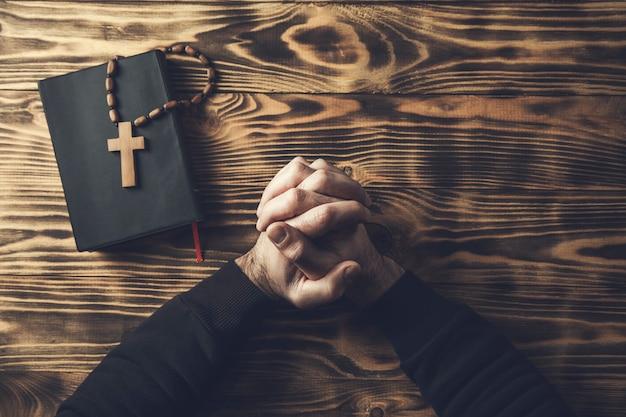 Mão de homem de oração cruzada na bíblia sagrada na mesa de madeira