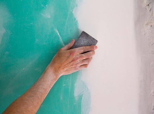 Mão de homem de reboco lixar o plaste na costura drywall