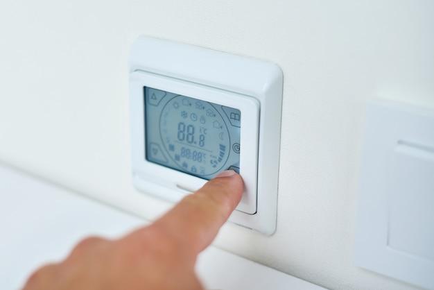 Mão de homem, definindo a temperatura no painel de controle de piso radiante