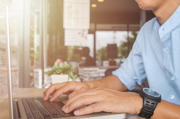 Mão de homem digitando em um teclado de computador portátil. conceito online de internet de tecnologia de negócios.