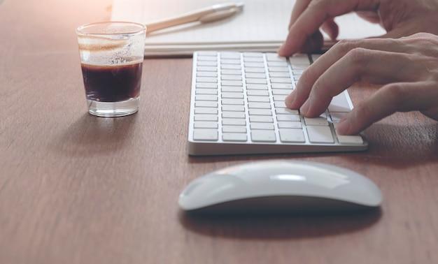 Mão de homem, digitando no teclado do computador branco enquanto está sentado na mesa de madeira com café quente.