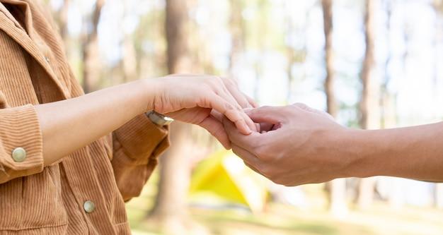 Mão de homem e mulher tocando segurando juntos no fundo do parque natural ao ar livre para o conceito de amor