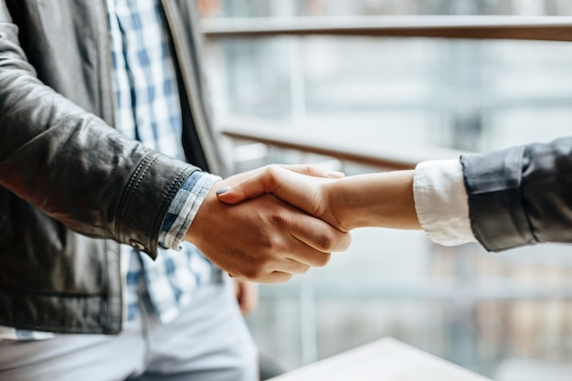 Mão de homem e mulher tremendo. aperto de mão após boa cooperação, empresária, apertando as mãos com empresário profissional após discutir um bom negócio. conceito de negócios.